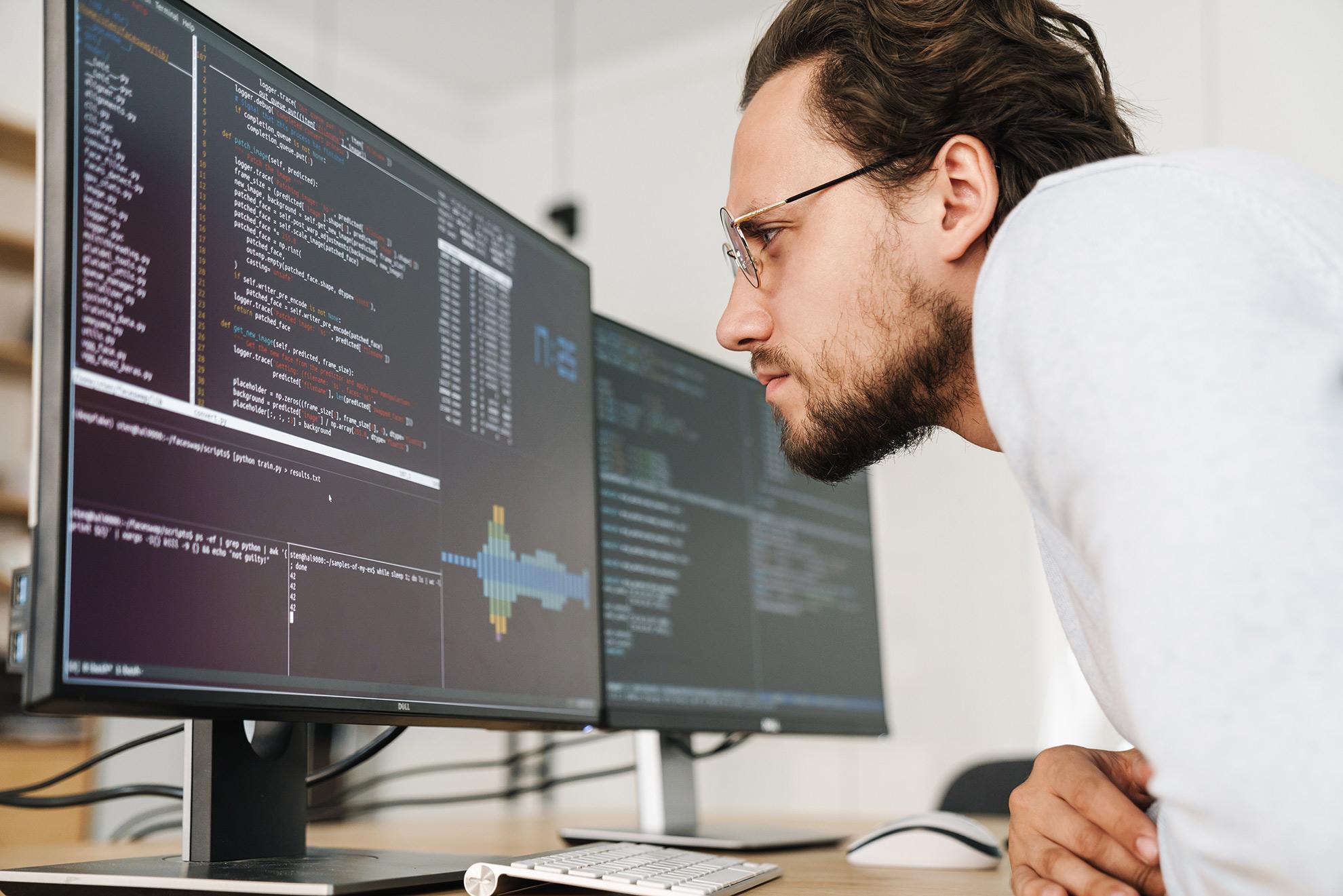 Programista wpatrujący się w kod, ilustracja do artykułu