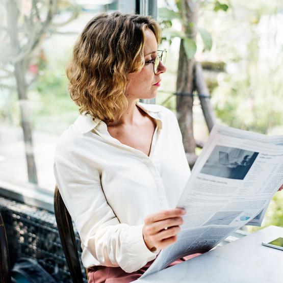 Kobieta czytająca gazetę - ilustracja do artykułu o wcięciach tekstu